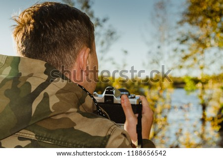 A photographer dressed in camouflage jacket with film camera in his hands takes pictures on the shore of a lake or river. Closeup back view.