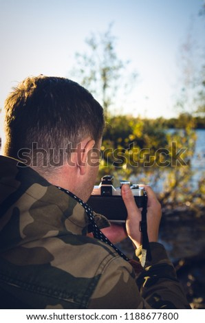A photographer dressed in camouflage jacket with film camera in his hands takes pictures on the shore of a lake or river. Back view with darkening effect.
