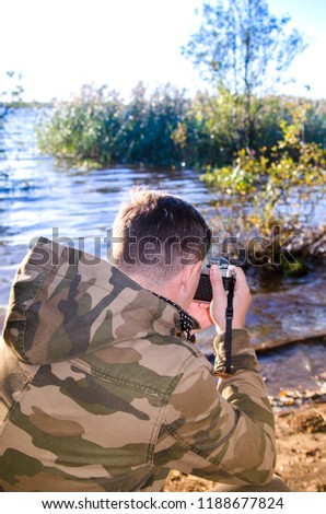 A photographer dressed in camouflage jacket with film camera in his hands takes pictures on the shore of a lake or river. Back view blue color toned.