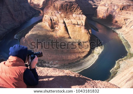 A photographer is taking picture and filming Horseshoe Bend in Arizona, USA
