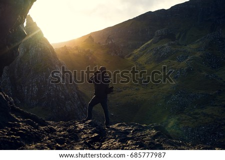 A photographer is working. After a beautiful hike in the mountain, he appreciates the sunset and gets this magic moment. The nature simply. The mountain and its green grass under orange sun. - Shutterstock ID 685777987