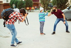 A photographer journalist shoot how young father and son bump elbows. New greeting style with elbows. Family in protection face mask outdoors. New idea for greetings. Coronavirus quarantine.