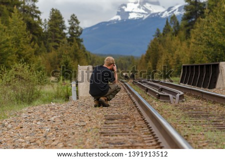 A photographer take a photo of two grizzly bears on the rail tracks