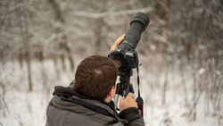 A photographer taking a shot of the beautiful forest with a digital camera