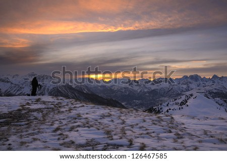 A photographer who looks at the horizon in the mountains of Montgenevre