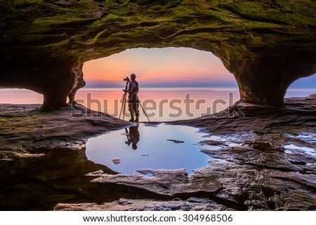 A photographer with tripod, standing in the mouth of a Michigan sea cave, is silhouetted by a colorful sunset over Lake Superior.