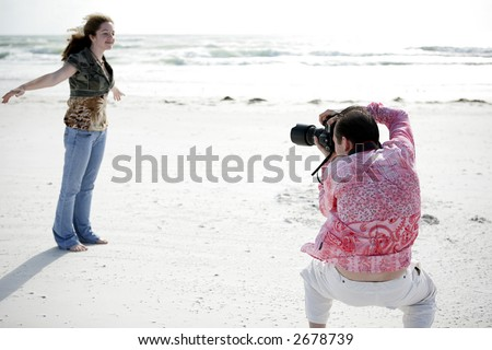 A photographer working with a model to get the right pose. Shallow depth of field with focus on photographer's head.