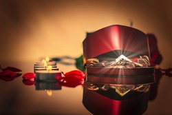 a photographic image of a brightly glowing gem in a box of chocolates heart shape against a background of burning small candles and flower petals vignetting effectfor congratulations on March 8