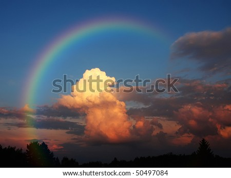 A photography of a white cloud in the evening sun under a rainbow #50497084