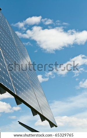 A photovoltaic solar panel array with a blue sky and puffy white clouds in the background.