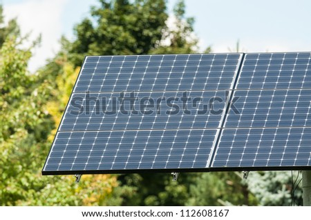A photovoltaic solar panel stands in front of green trees.