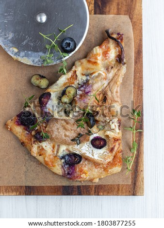 A piace of homemade rustic pizza with brie cheese, pears, blueberries and thyme Stock fotó ©