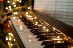 A piano with christmas lights and tree