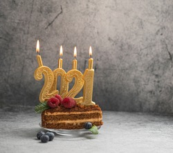 A pice of Christmas cake with burning candles-numbers 2021, decorated with berries on a gray background with copy space.