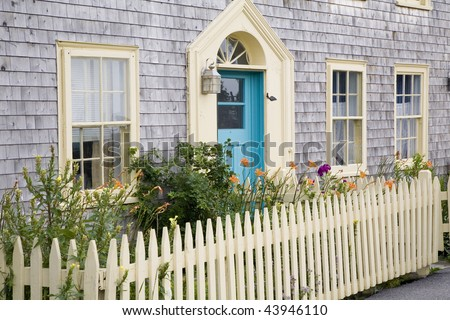 A picket fence surrounds a small garden by the front of an older style vintage home with a blue door.