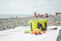 A picnic bag, bread and fruit on a tablecloth on the beach by the sea.