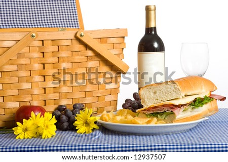 A picnic lunch consisting of a sandwich, potato chips and grapes on a Blue gingham or checked tablecloth