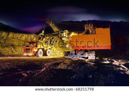 A picture of a big yellow mining truck at worksite (night)