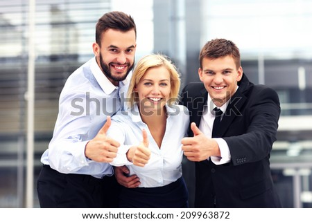 A picture of a cheerful business team outside modern building