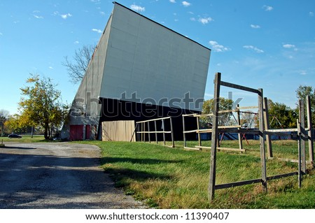 A picture of a closed drive in movie theater with weeds growing where cars once were