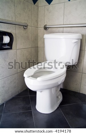 A picture of a commode with no lid and handicap accommodations.