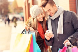 A picture of a couple shopping with smartphone in the city