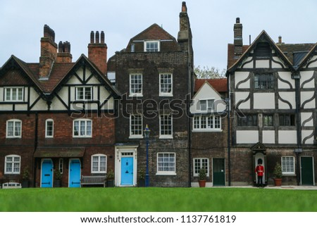 A picture of a few old rural british houses with blue door and with a beefeater guard in front of one of them.