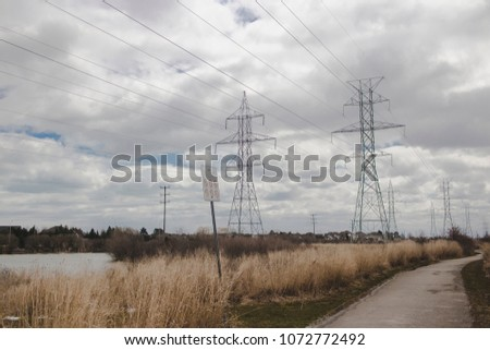 A picture of a field with transmission towers in the background on a cloudy day #1072772492