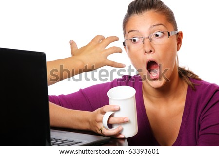 A picture of a hand coming out of computer and trying to catch a terrified young woman