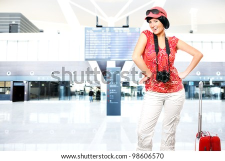 A picture of a happy woman with camera and suitcase waiting at the airport