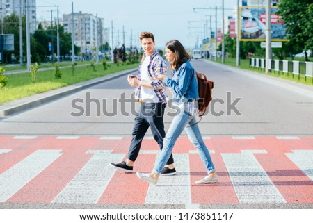 A picture of a happy young couple students on a walk on a day off. A happy friends crosses the road at a pedestrian crossing. Side view