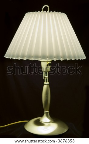A picture of a lovely little brass lamp taken against a black backdrop.