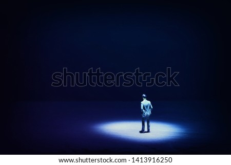 A picture of a miniature man stands in the spotlight looking forward .Concept of facing the unknown, taking a decision and finding solution.