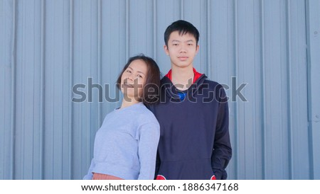 A picture of a mother and a teenage son. Teenage son Taller than mother Happy family. The background is a pattern set from a metal container. An Asian mother with short black hair looks happy. Foto stock ©