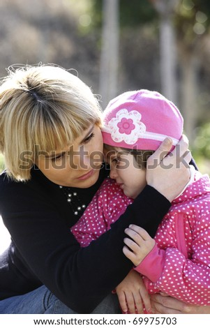 A picture of a mum comforting and hugging her baby girl in the park