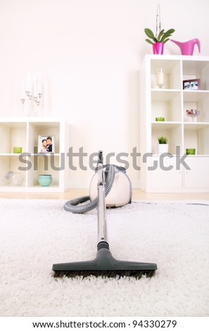 A picture of a new vacuum cleaner standing in the living room