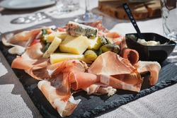 A picture of a plate of speck and typical italian salami with cheese and pickles, Cortina D'Ampezzo, Italy