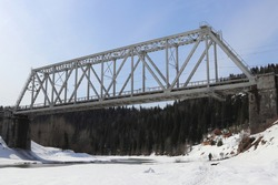 A picture of a railway bridge over the Usva River in the Ural Mountains. Perm Territory, Russia. Beautiful landscape with an architectural structure.