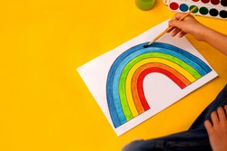 A picture of a rainbow brush and watercolor on a white sheet. Painted rainbow by the hands of a child on a yellow background. Chase rainbow. Place for text. Quarantine.