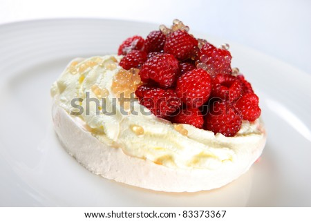 A picture of a raspberry Pavlova meringue served with caviar on a white plate