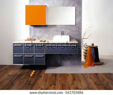 A picture of a sparkling modern bathroom design in a gray theme. Includes wall mounted bathroom cabinets, mirror and sink.