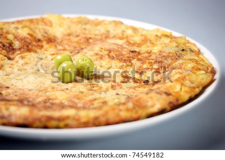 A picture of a typical Spanish tortilla decorated with olives over light background