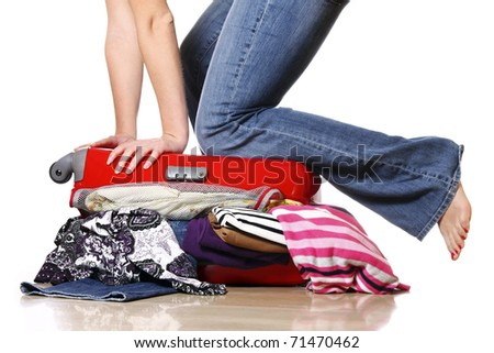 A picture of a woman having problem with packing a suitcase