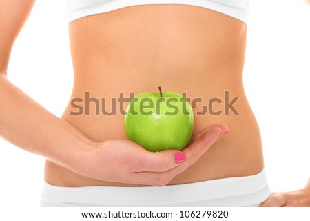 A picture of a woman holding a green apple in front of her fit belly