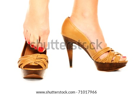 A picture of a woman standing against white background and putting on shoes
