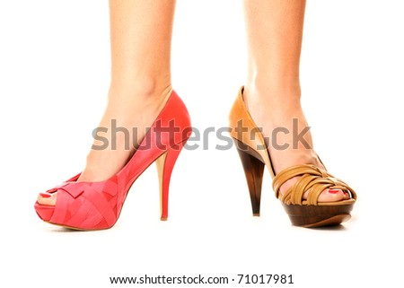 A picture of a woman standing against white background in two different shoes - stock photo