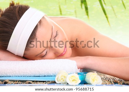 A picture of a young beautiful woman relaxing in a spa center