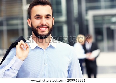 A picture of a young businessman standing outside modern building