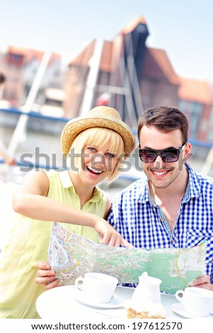 A picture of a young couple pointing at map in a restaurant