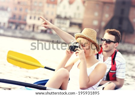 A picture of a young couple taking pictures in a canoe